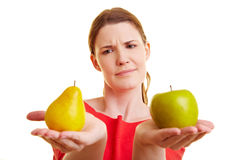 Woman comparing apple and pear royalty free stock photo