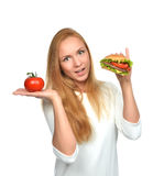 Woman comparing tasty unhealthy burger sandwich in hand and toma Royalty Free Stock Photography