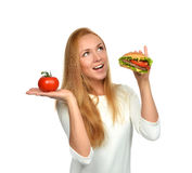 Woman comparing tasty unhealthy burger sandwich in hand and toma Stock Images