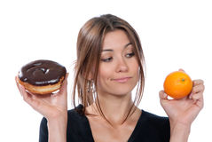 Woman comparing unhealthy donut and orange fruit Royalty Free Stock Photo
