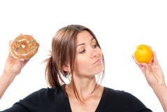 Woman comparing unhealthy donut and organic orange Stock Photography