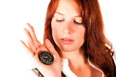 Woman with compass. Beautiful red-headed girl is holding a compass near her face. The compass is pointing to the north royalty free stock images