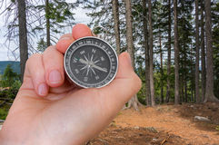 Woman with compass is seeking a right way in forest Royalty Free Stock Image