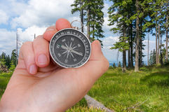 Woman with compass is seeking a right way in forest Royalty Free Stock Photography