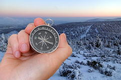 Woman with compass is seeking a right way in mountains Stock Image
