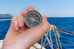 Woman with compass is seeking a right way on sea Stock Photo