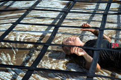 Woman competing and struggling in mud in obstacle course. A participant in the Gladiator Rock-n-Run event at the Rose Bowl in Pasadena in 2014. Competitors must royalty free stock photos