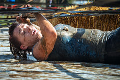 Woman competing and struggling in mud in obstacle course. A participant in the Gladiator Rock-n-Run event at the Rose Bowl in Pasadena in 2014. Competitors must stock images