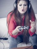 Woman complaining at gaming pad. Woman being angry while playing video game holding gaming pad and complaining stock photography