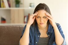 Woman complaining suffering migraine at home. Front view portrait of a woman complaining suffering migraine sitting on a couch in the living room at home stock image