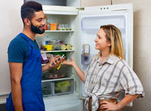 Woman complaining to black handyman on problems with fridge. White smiling women complaining to black handyman on problems with fridge Stock Photography
