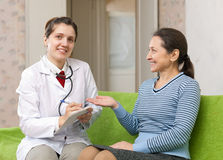Woman complaining to  doctor about feels Royalty Free Stock Photography