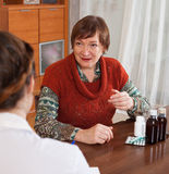 Woman complaining to  doctor about feels Royalty Free Stock Images