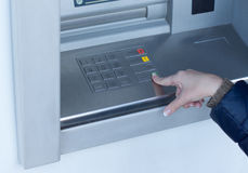 Woman completing a transaction on an ATM. Outside a bank as she withdraws cash for personal spending Royalty Free Stock Photo