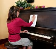 Woman composing piano music Royalty Free Stock Photos