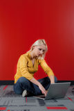 Woman with computer. Young blond woman with computer sitting on the floor, red wall background Royalty Free Stock Photo