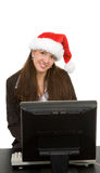 Woman on Computer. Woman wearing a Santa hat looking over her computer.  Isolated against a white background Stock Photo
