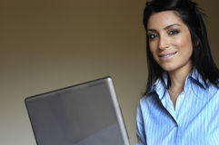 Woman at computer. Glad woman working at computer and looking to the camera stock photos