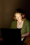 Woman at Computer. Redhead woman in darkened room working on a laptop. She is wearing a green shirt. The wall behind has a painted texture Stock Images