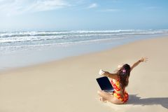 Woman with computer on beach Stock Photos