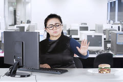 Woman with computer and burger in office Stock Photos
