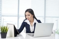 Woman on computer desk writing on a calendar royalty free stock photography