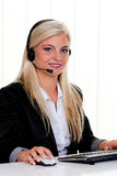 Woman at computer with headset and Hotline. Young woman with headset at computer hotline. Friendly Clerk Royalty Free Stock Photography