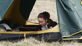 Woman with the computer inside the tent. Woman working at a computer inside the tent stock footage