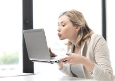 Woman with computer kissing the screen Royalty Free Stock Images
