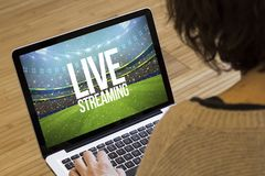 Woman computer live streaming. Live streaming concept: live streaming text on a stadium on a laptop screen. Screen graphics are made up royalty free stock images