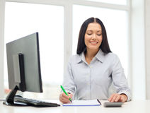 Woman with computer, notebook and calculator Stock Photography