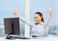 Woman with computer, papers showing thumbs up Stock Images
