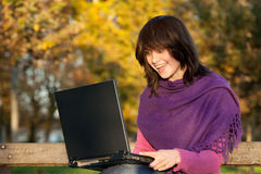 Woman with computer on park bench Stock Image