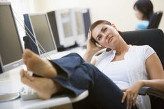 Woman in computer room with feet up thinking. Hand resting on her head Stock Image