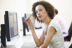 Woman in computer room thinking. Holding a pencil Royalty Free Stock Image