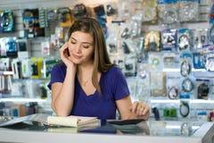 Woman Computer Shop Owner Examining Bills And Taxes royalty free stock photo