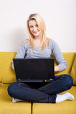 Woman with computer sitting on couch Stock Photo