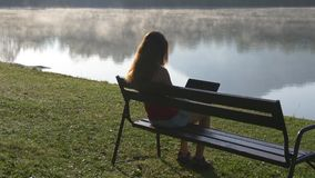Woman with computer sitting near mountain lake stock video