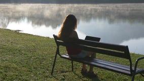 Woman with computer sitting near mountain lake stock video