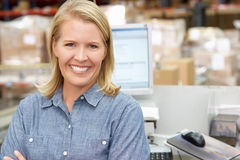 Woman At Computer Terminal In Distribution Warehouse. Smiling Royalty Free Stock Photo