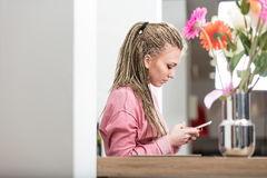 Woman concentrated in sending messages. Woman on dreadlocks, texting with her mobile cell phone in a kitchen relaxed and happy Royalty Free Stock Image