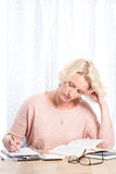 Woman Concentrates While Reading and Writing at wooden Table Royalty Free Stock Photos