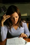 Woman concentrating. Woman with dark hair lavender sweater reviewing a budget Stock Images