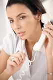 Woman concentrating on call. Attractive woman concentrating on landline phone call, thinking, holding pen stock images