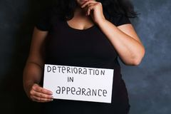 Woman concerned about appearance deterioration. Sad woman worried and concerned about appearance deterioration. Overweight, beauty and health concept stock image
