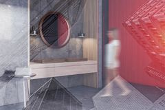Woman in concrete bathroom corner, double sink. Woman in corner of modern bathroom with concrete and red walls, concrete floor, double sink standing on wooden royalty free stock photography