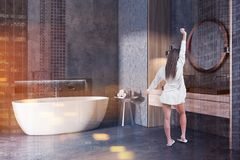 Woman in concrete bathroom corner, tub and sink. Woman in corner of modern bathroom with concrete walls and floor, white bathtub, shelf with mirror and shampoos royalty free stock photography