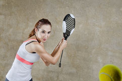 Woman in concrete paddle tennis court ready for backhand shot Stock Image