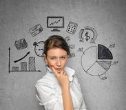 Woman on concrete wall with business sketches Stock Photography