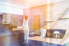 Woman in concrete and wood bathroom corner royalty free stock images